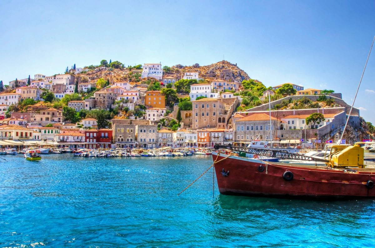 A view of the beautiful Greek island, Hydra. There is a fishing boat on the foreground and some local architecture on the background. The view is from the sea as the cruise ship embarked in Hydra.