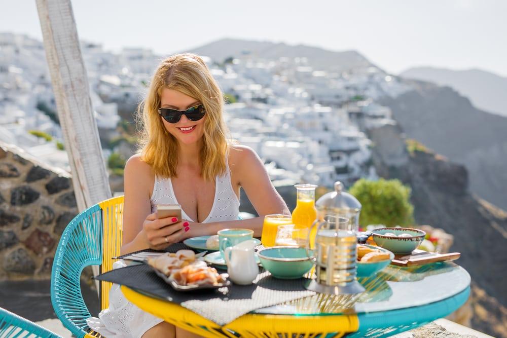 Woman using mobile phone while having breakfast in Santorini